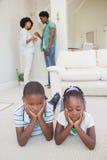 Enfants de mêmes parents heureux s'asseyant sur le plancher utilisant l'ordinateur portable Photographie stock libre de droits