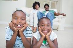 Enfants de mêmes parents heureux se trouvant sur le plancher Image libre de droits