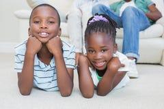 Enfants de mêmes parents heureux se trouvant sur le plancher Photographie stock libre de droits