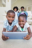 Enfants de mêmes parents heureux se trouvant sur le plancher utilisant le comprimé Image libre de droits