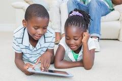 Enfants de mêmes parents heureux se trouvant sur le plancher utilisant le comprimé Photo stock