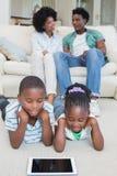 Enfants de mêmes parents heureux se trouvant sur le plancher utilisant le comprimé Photos libres de droits