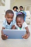 Enfants de mêmes parents heureux se trouvant sur le plancher utilisant le comprimé Photographie stock libre de droits