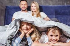 Enfants de mêmes parents heureux sous la couette Photographie stock libre de droits