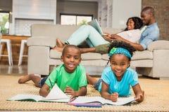 Enfants de mêmes parents heureux sur le dessin de plancher Photos libres de droits