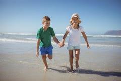 Enfants de mêmes parents heureux tenant des mains tout en courant à la plage Photos libres de droits