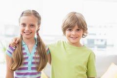 Enfants de mêmes parents heureux tenant le bras autour à la maison image libre de droits