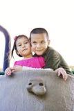 Enfants de mêmes parents hispaniques heureux ensemble à la cour de jeu Photographie stock