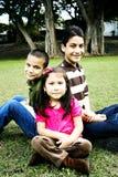 Enfants de mêmes parents hispaniques heureux ensemble devant l'arbre Photographie stock