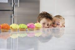Enfants de mêmes parents jetant un coup d'oeil au-dessus du compteur sur la rangée des petits gâteaux Images stock