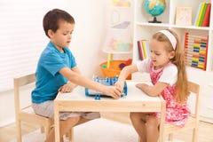 Enfants de mêmes parents jouant aux échecs dans la salle du gosse Photos libres de droits