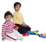 Enfants de mêmes parents jouant avec des blocs Photo stock
