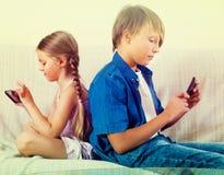 Enfants de mêmes parents jouant avec des smartphones sur le sofa Photo stock