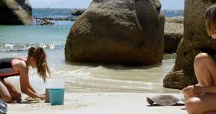 Enfants de mêmes parents jouant avec le sable dans la plage 4k banque de vidéos