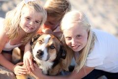 Enfants de mêmes parents jouant avec leur chien Photo stock