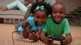 Enfants de mêmes parents jouant des jeux vidéo sur le plancher tandis que montre de parents banque de vidéos