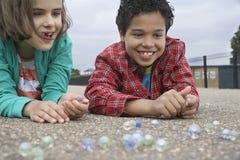 Enfants de mêmes parents jouant des marbres sur le terrain de jeu Photographie stock libre de droits