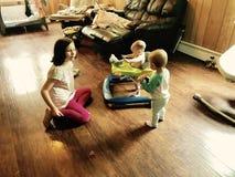 Enfants de mêmes parents jouant ensemble dans le salon photo libre de droits