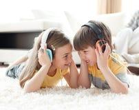 Enfants de mêmes parents jouant sur l'étage avec des écouteurs Image stock