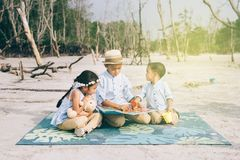 Enfants de mêmes parents lisant et riant ensemble dehors le port occasionnel images stock