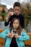 Enfants de mêmes parents mangeant le gâteau Photos libres de droits