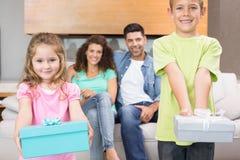 Enfants de mêmes parents montrant des présents devant des parents sur le divan Images stock