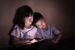 Enfants de mêmes parents observant le comprimé examiner ensemble dans la faible lumière Images libres de droits