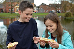 Enfants de mêmes parents partageant la pâtisserie Images libres de droits