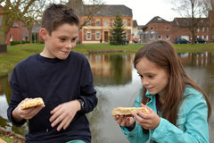 Enfants de mêmes parents partageant la pâtisserie photo stock