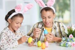 Enfants de mêmes parents peignant des oeufs de pâques Image stock