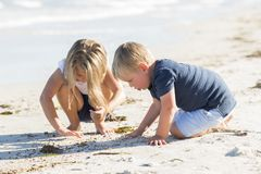 Enfants de mêmes parents peu adorables et doux jouant ensemble en plage de sable avec petit étreindre de frère et la belle jeune  Photos libres de droits