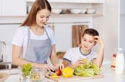 Enfants de mêmes parents positifs faisant cuire dans la cuisine ensemble Image stock