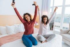 Enfants de mêmes parents rayonnants soulevant des bras tout en célébrant la victoire dans le jeu visuel Images libres de droits