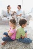 Enfants de mêmes parents s'asseyant de nouveau au dos tandis que les parents discutent Photo stock