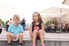 enfants de mêmes parents s'asseyant sur une étape à un centre de la ville Photographie stock libre de droits