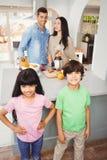 Enfants de mêmes parents se tenant à la table avec des parents préparant le jus de fruit Images stock