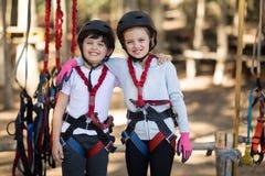 Enfants de mêmes parents se tenant ainsi que le bras autour en parc Photo libre de droits