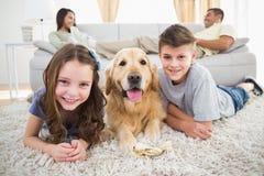Enfants de mêmes parents se trouvant avec le chien tandis que parents détendant sur le sofa Photo libre de droits