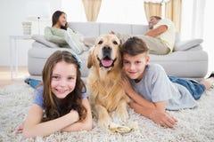Enfants de mêmes parents se trouvant avec le chien tandis que parents se reposant sur le sofa Image libre de droits