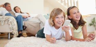 Enfants de mêmes parents se trouvant sur le plancher regardant la TV Photographie stock libre de droits