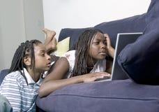 Enfants de mêmes parents sur l'ordinateur Images libres de droits