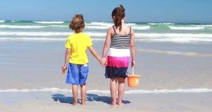 Enfants de mêmes parents tenant des mains et la position sur la plage banque de vidéos