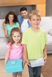 Enfants de mêmes parents tenant des présents devant des parents sur le divan Photographie stock