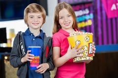 Enfants de mêmes parents tenant le maïs éclaté et la boisson au cinéma photo stock