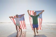 Enfants de mêmes parents tenant les drapeaux américains tout en courant à la plage Photographie stock