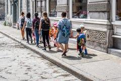 Enfants de marche de jeunes professeurs petits le long de rue Photographie stock libre de droits