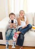 Enfants de mêmes parents heureux regardant la TV Images libres de droits