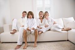 Enfants de mêmes parents jouant le jeu vidéo tandis que montre de parents Photographie stock