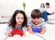Enfants de mêmes parents mignons jouant des jeux vidéo Photo stock
