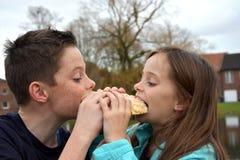 Enfants de mêmes parents partageant la pâtisserie Image stock